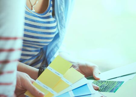 paint swatch: Couple choosing paint colour from swatch for new home sitting on wooden floor.