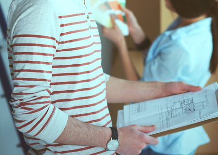 paint swatch: Couple choosing paint colour from swatch for new home .