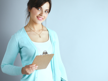 Woman with folder for documents on gray  background . Stock Photo