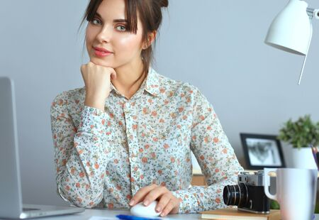 Portrait of  young woman sitting at  desk .
