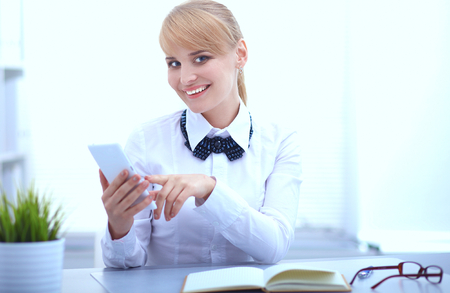 phonecall: Woman in office using mobile phone .