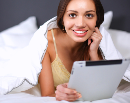 noon: Women use a tablet pc on the bed .