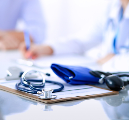 Doctor mujer sentada con paciente masculino en el escritorio. Foto de archivo