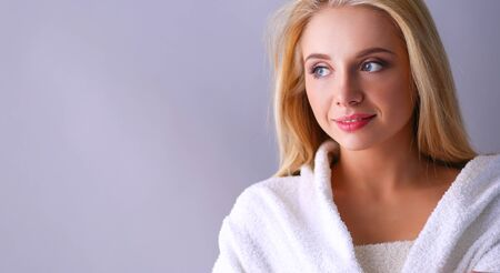 be6fb47bf44670 #66788723 - Lächelnde Frau im weißen Bademantel, lokalisiert auf grauem  Hintergrund.