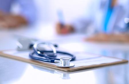 Doktor Frau mit männlichen Patienten sitzen am Schreibtisch Standard-Bild - 74718864