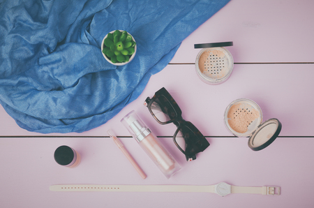 finery: Sunglasses, cosmetics makeup and essentials on wooden background