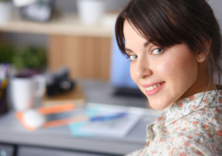 Portrait of young woman sitting at desk Stock Photo