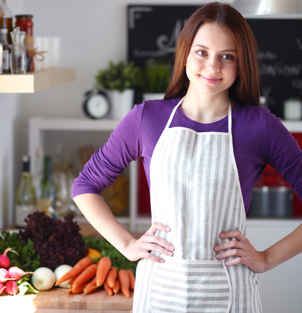 kitchen furniture: Young woman standing in her kitchen near desk Stock Photo