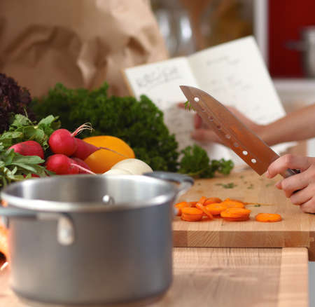 Young woman cutting vegetables in the kitchen Stock Photo
