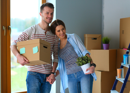 property ladder: Happy young couple unpacking or packing boxes and moving into a new home