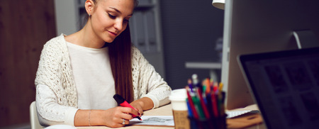 concentrate: Young woman working in office, sitting at desk