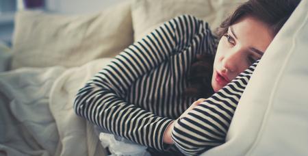 Portret van een zieke vrouw blaast haar neus zittend op de bank