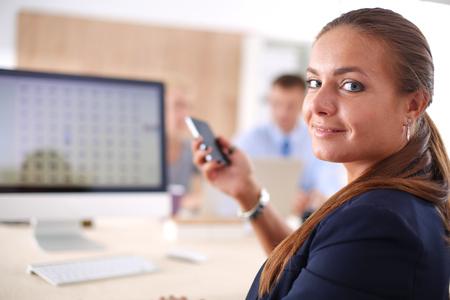 Junge Frau, die im Büro, sitzend am Schreibtisch mit Ordner arbeitet Standard-Bild - 83812753