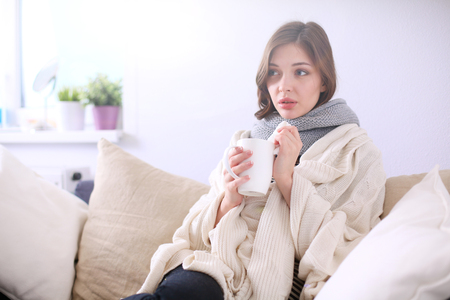Portrait of a sick woman blowing her nose while sitting on the sofa Reklamní fotografie - 83800565