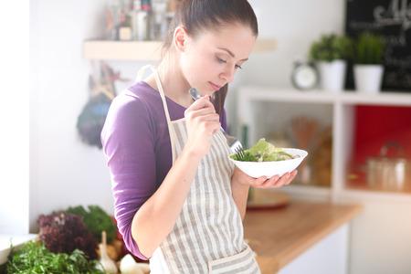 utensilios de cocina: Mujer joven que come ensalada fresca en la cocina moderna Foto de archivo