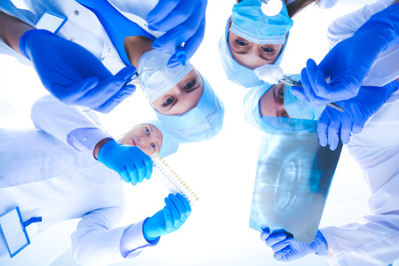 Surgeons team, woman wearing protective uniforms,caps and masks