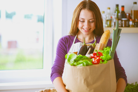 Young woman holding grocery shopping bag with vegetables Standing in the kitchen Stock Photo