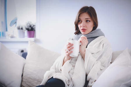 Portrait of a sick woman blowing her nose while sitting on the sofa Stock Photo