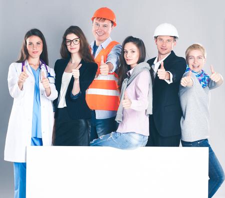 ブランクの看板を保持しているさまざまな職業の人々 の幸せなグループ。 写真素材