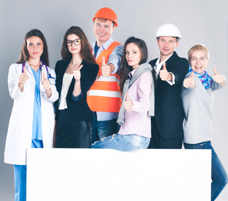 Happy group of people of different professions holding a blank billboard.
