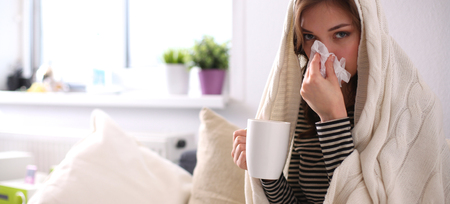 Portrait of a sick woman blowing her nose while sitting on the sofa Reklamní fotografie