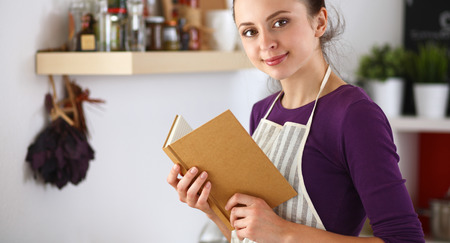 A young woman standing in the kitchen reading a cookbook.