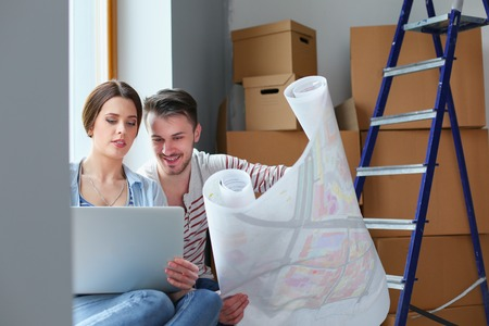 Young couple sitting on the floor and looking at the blueprint of new home. Young couple Stock Photo