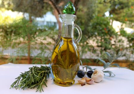 sprig: Olive oil in the bottle sprig of rosemary in the garden