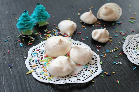 egg white: Meringue cakes out of the egg white and sugar white lacy napkin on a black table in the New Year and Christmas decorations