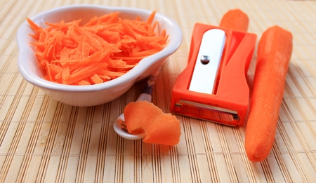grate: Fresh carrots grate on a grater for salad