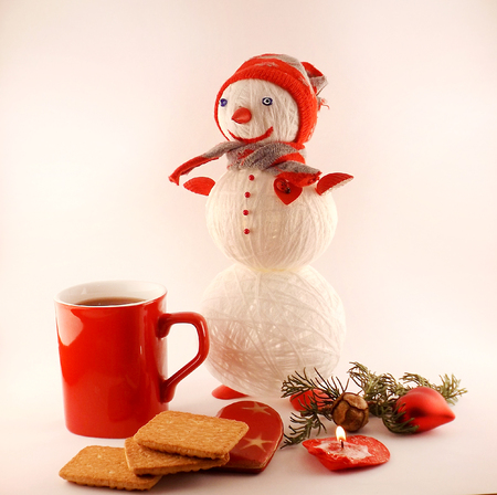 Tea with Christmas cookies and knitted snowman