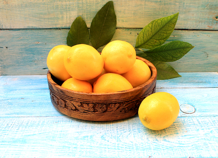 sarcastic: Ripe yellow lemons in a basket on a blue background