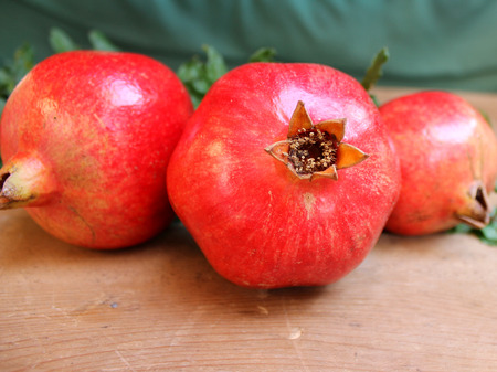 Ripe pomegranate fruit with a branch and leaves on a wooden table