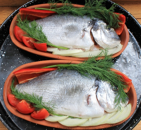 Fish dorado baked in the oven with vegetable garnish Stock Photo