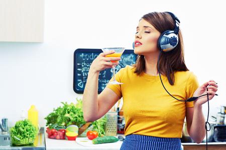 Vrouw koken met plezier Meisje drinken sap in de keuken en luisteren muziek