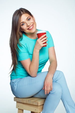 sitt: Smiling woman with long hair sitting on chair with coffee cup. Isolated.