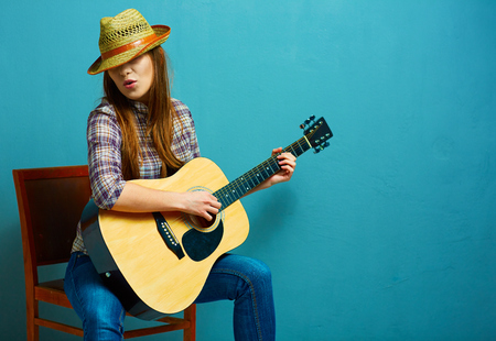 chairs: Singing young model play acoustic guitar. Stock Photo