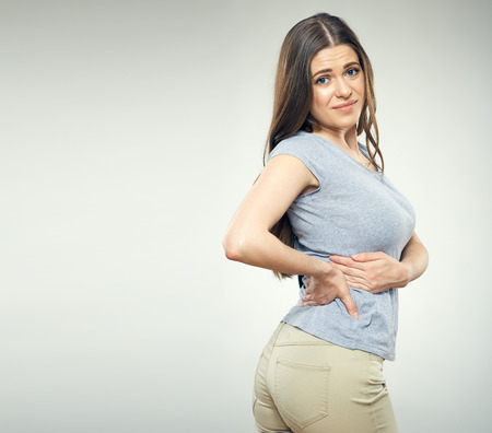 Young woman with back pain isolated portrait.