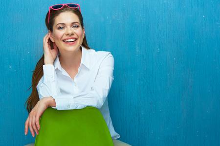 Glimlachende vrouw met zonnebril die op stoel tegen blauwe muur zetten. Stockfoto