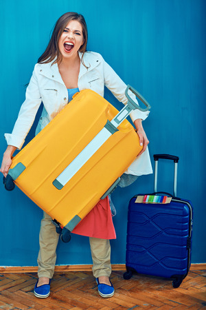 Woman holding heavy weight suitcase with clothes for vacation.