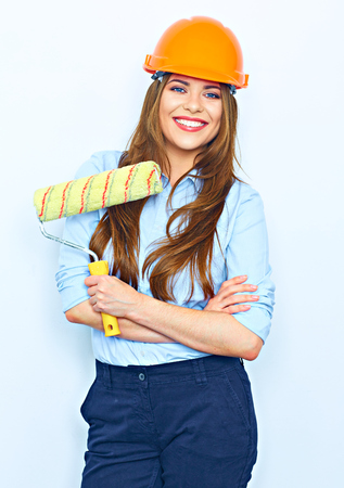 hair roller: Smiling business woman with crossed arms standing against wall with painting roller. Model wearing a building helmet.