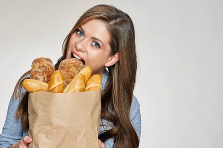 Hungry Woman bites bread from paper bag