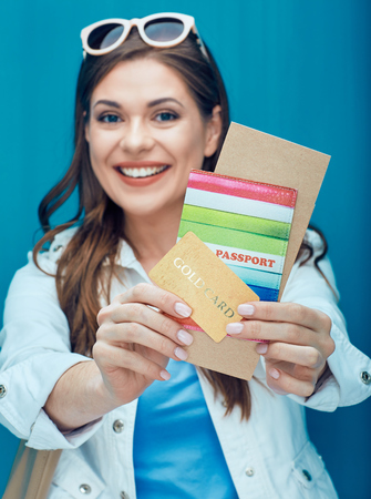 Happy woman showing passport, credit card and ticket for holidays. Blue background.