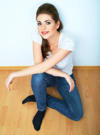 white wood floor: Smiling girl sit on a floor. White background isolated. Stock Photo