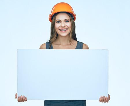 Het glimlachen vrouw het dragen beschermt bouwershelm die witte banner met duidelijke exemplaarruimte houden. geïsoleerd portret. Stockfoto