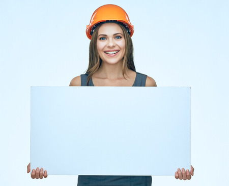 Smiling woman wearing protect builder helmet holding white banner with clear copy space. isolated portrait.