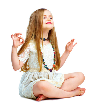 girl child with long blond hair siting on a floor in yoga lotus pose. isolated on white background.