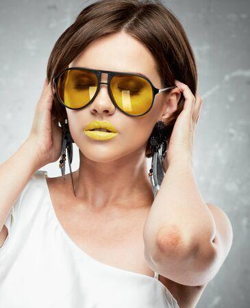 pelo castaño claro: Retrato de belleza de mujer joven con gafas de sol amarillo. Cara conmovedora de mano. Hermosa modelo.