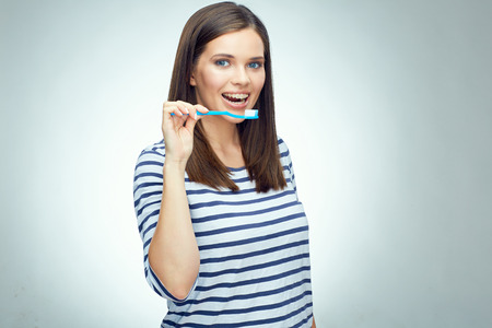Smiling girl with brace brushing teeth. Teenager toothy problem. isolated portrait.