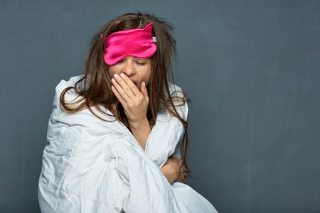 Portrait of yawning woman with blanket. Sleep disorders concept.